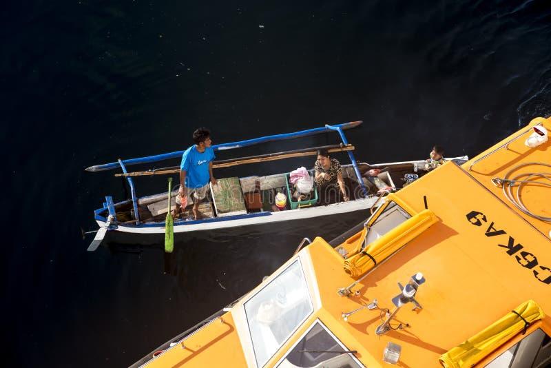 Pêcheur indonésien vendant les poissons fraîchement pêchés directement du bateau images stock