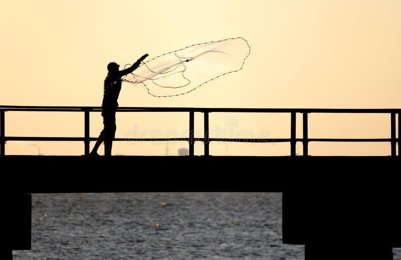 Pêcheur jetant le réseau en l'air photos stock
