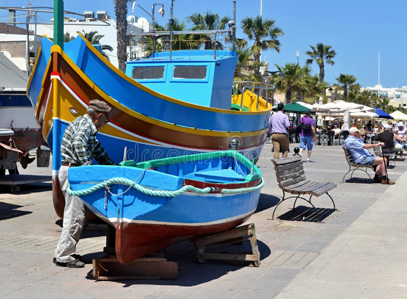 Pêcheur maltais vérifiant son bateau, Marsaxlokk image stock