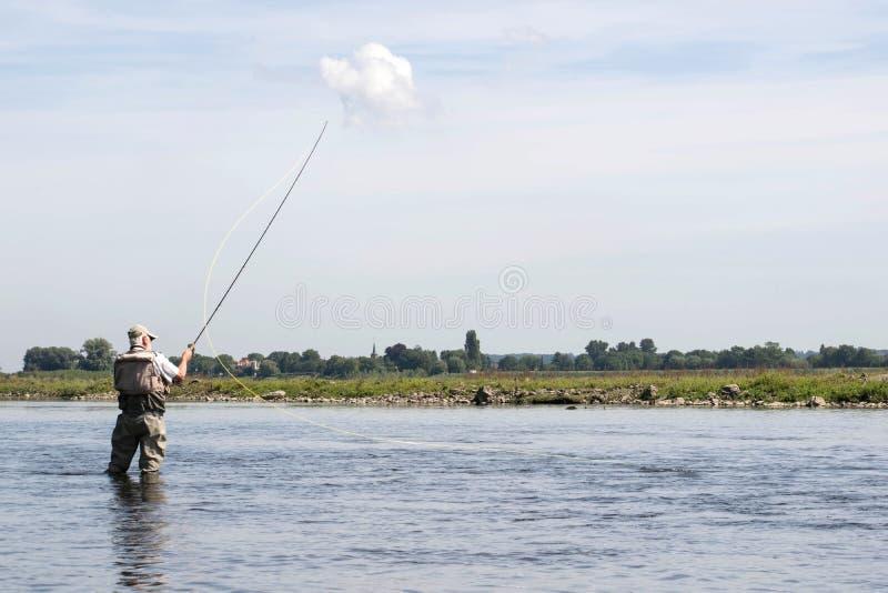 Pêcheur masculin se tenant en rivière avec des attirails de pêche de mouche photographie stock