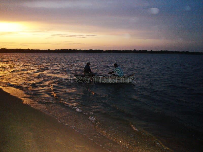 Pêcheur mozambicain sur le chemin de la maison dans le bateau de leur pêcheur photographie stock