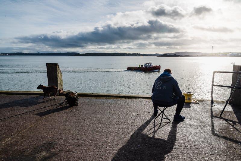 Pêcheur s'asseyant sur le dock de la baie photographie stock libre de droits