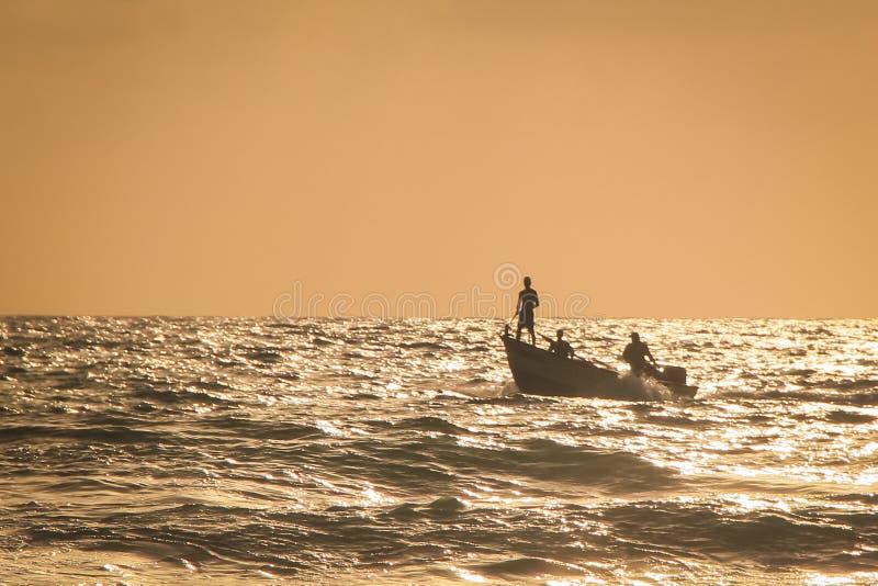 Pêcheur se tenant sur un bateau au coucher du soleil de mer image libre de droits
