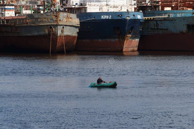 Pêcheur seul sur le bateau près du grand bateau photographie stock
