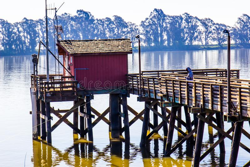 Pêcheur solitaire On Pier At Rivers Shoreline photographie stock libre de droits