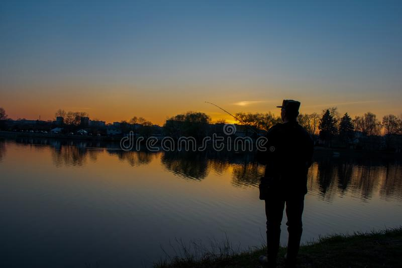 Pêcheur sur la rivière foncée photo stock