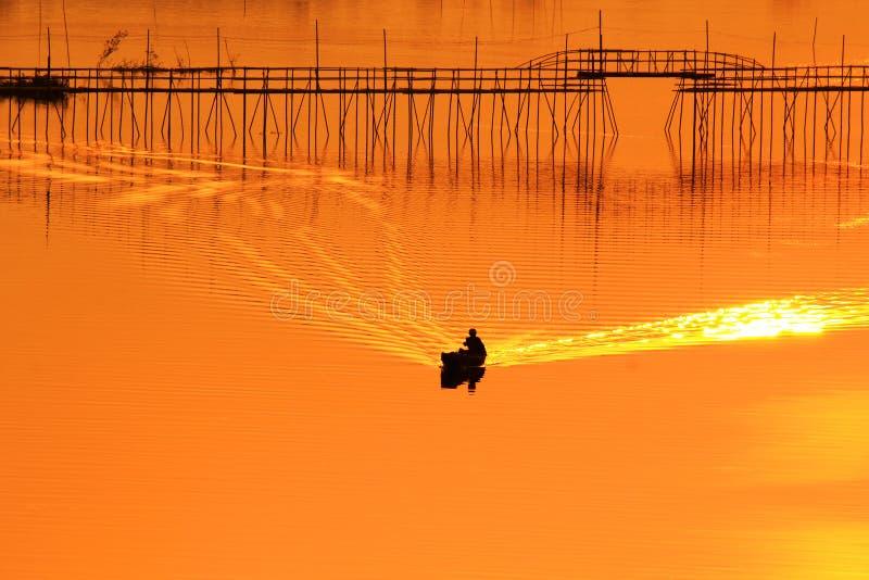 Pêcheur sur le bateau avançant rivière photo libre de droits