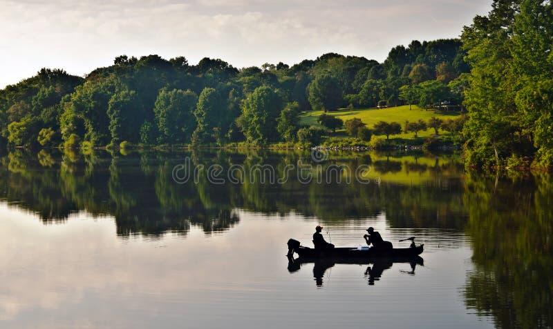 Pêcheur sur le lac au lever de soleil photos libres de droits