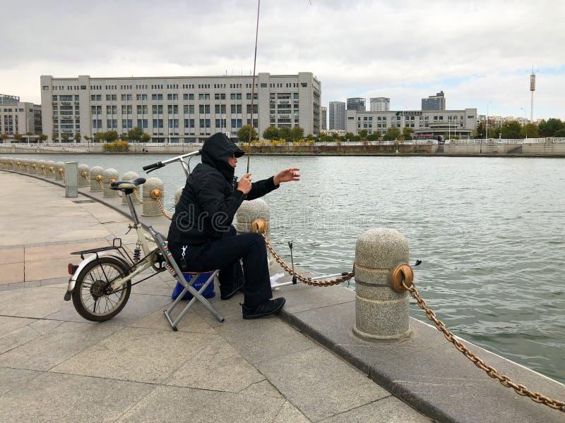 Pêcheur sur le remblai de la rivière Haihe dans le centre ville de Tianjin, Chine photos stock