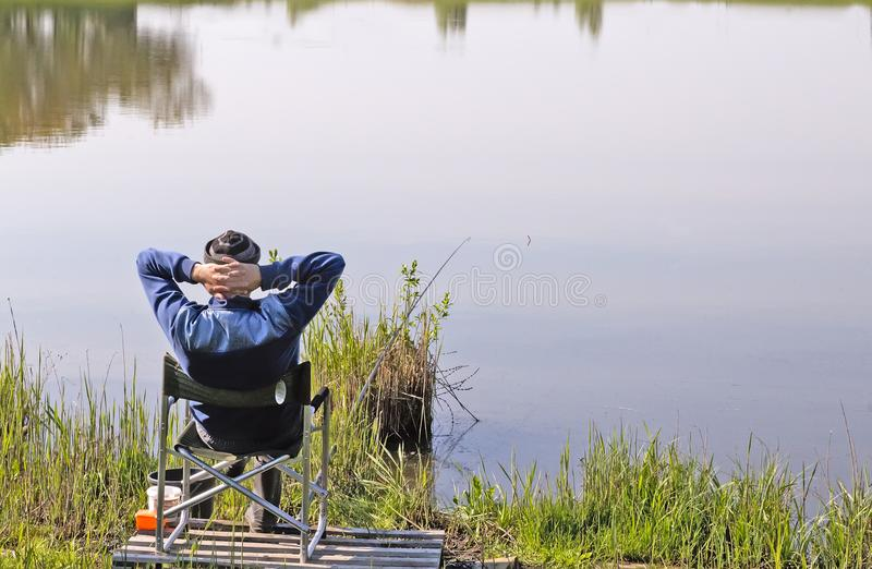 Pêcheur sur le rivage d'un grand lac photos stock