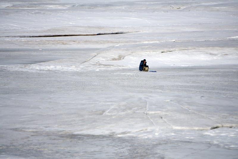 Pêcheur sur un lac au jour ensoleillé d'hiver photo libre de droits