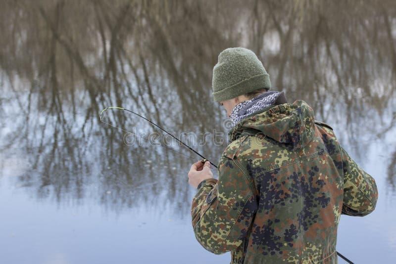 Pêcheur tenant un attrait dans sa main il vérifie l'amorce avant la pêche image libre de droits