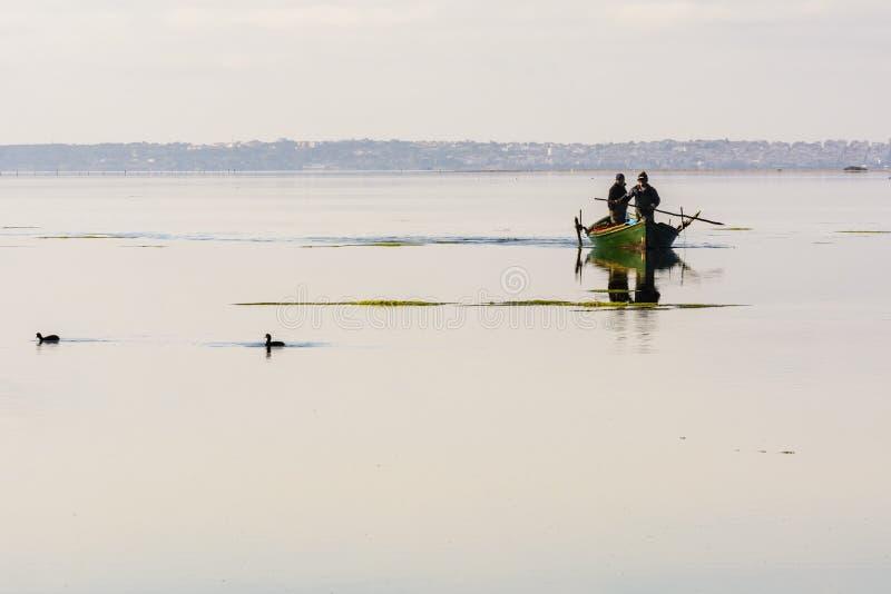 Pêcheurs avec leurs bateaux antiques, chute à l'aube Sud de la Sardaigne occidentaux images libres de droits