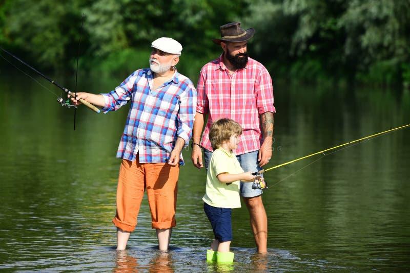 Pêcheurs de famille pêchant avec la bobine de rotation Garçon avec la pêche de père et première génération de mouche extérieure a photographie stock libre de droits