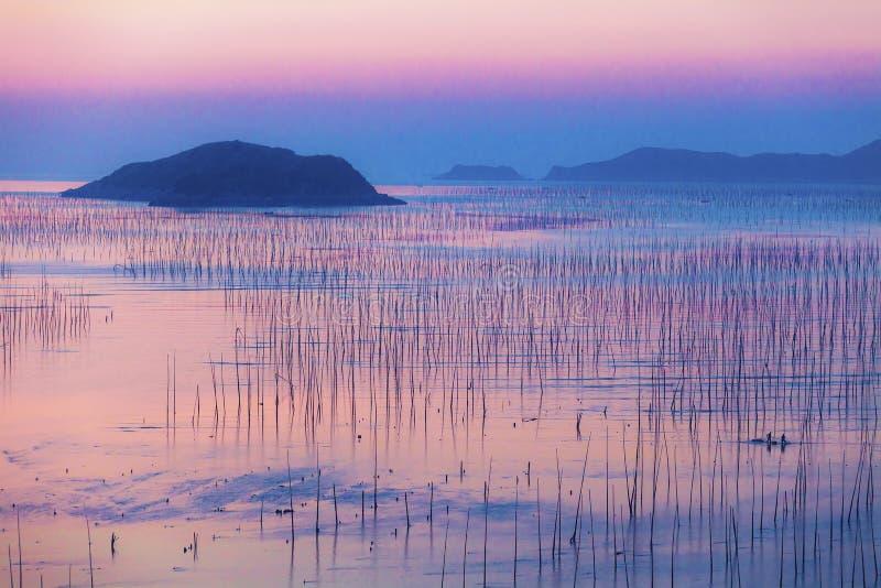 Pêcheurs et île au bord de la mer au lever de soleil image libre de droits