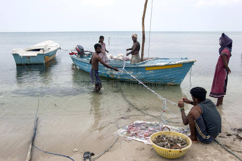 Pêcheurs et femmes s'occupant leurs filets sur l'île de Delft dans la région du nord de Jaffna dans Sri Lanka photo libre de droits