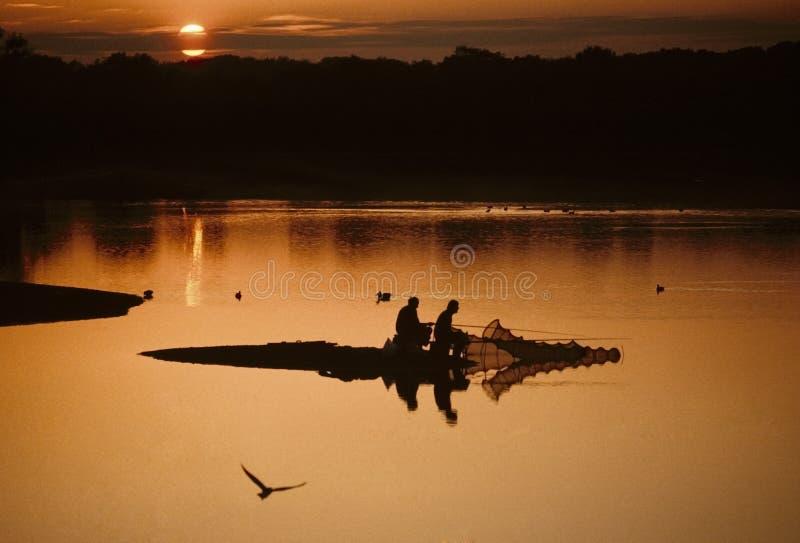 Pêcheurs pêchant sur le lac avec le coucher du soleil derrière image stock