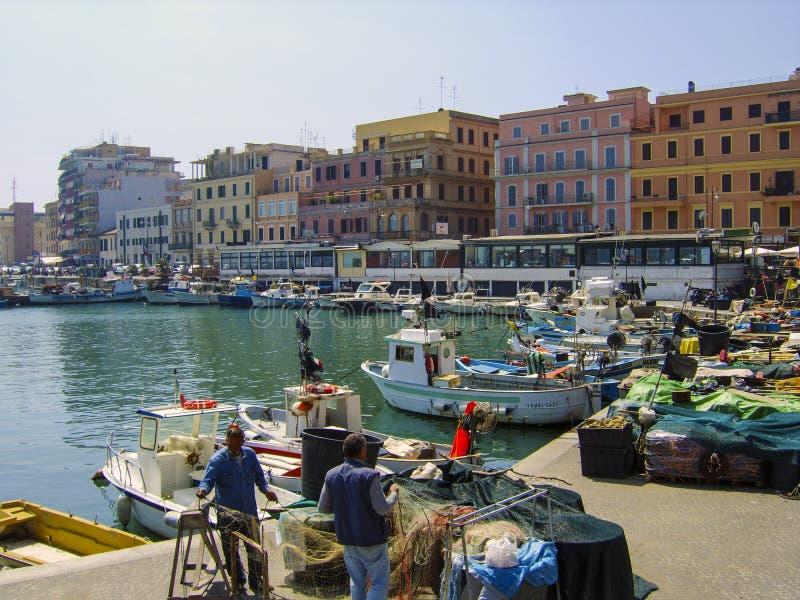 Pêcheurs réparant et préparant leurs filets sur le bord du quai chez Anzio, au sud de Rome, l'Italie images stock