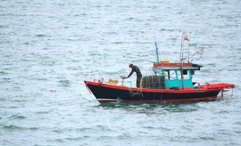 Pêcheurs sur de petits bateaux de pêche près de l'île image stock