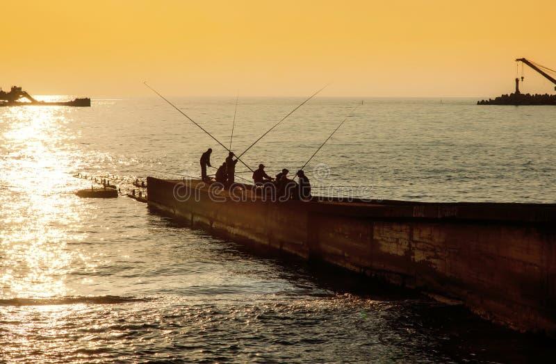 Pêcheurs sur le pilier sur le fond du coucher du soleil photographie stock libre de droits
