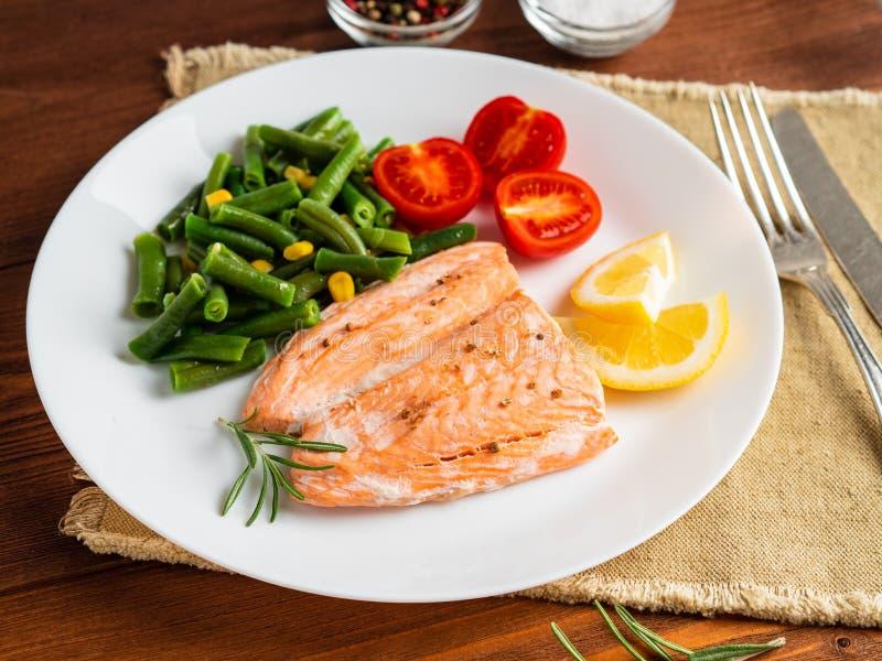 Pêchez les saumons cuits à la vapeur avec des légumes La nourriture d'alimentation saine, obscurité courtisent photographie stock libre de droits