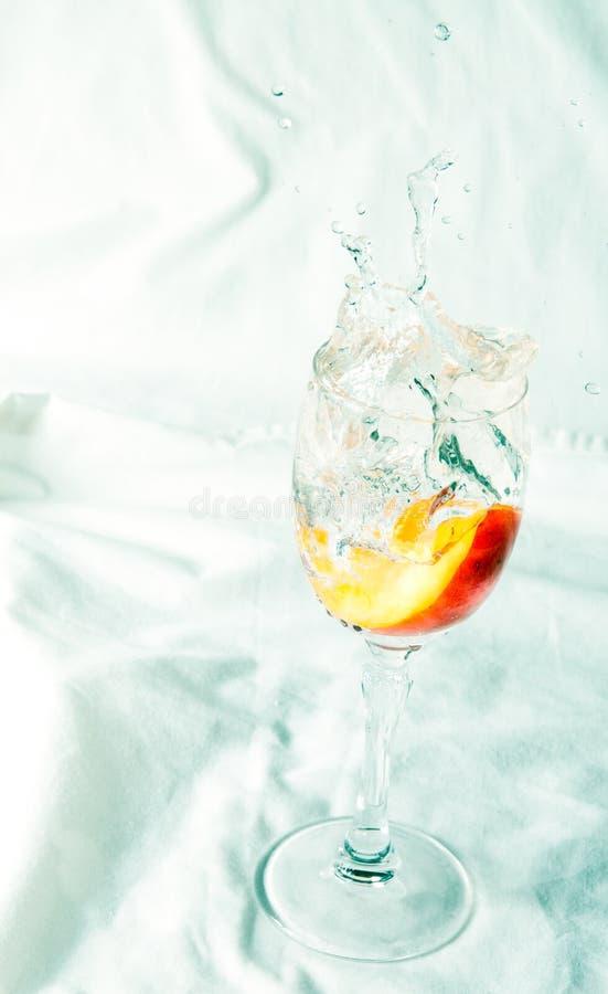 Pêssego e respingo da água em um vidro fotos de stock royalty free