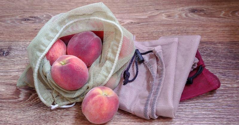 Pêssegos em sacos reusáveis do eco para frutas e legumes na superfície de madeira imagens de stock