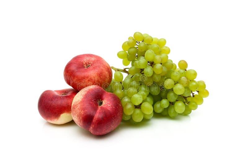 Pêssegos lisos chineses e um grupo de uvas verdes no backgr branco imagens de stock royalty free