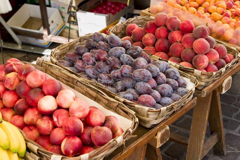 Pêssegos, nectarina, bannanas e ameixas nas cestas em um mercado imagem de stock