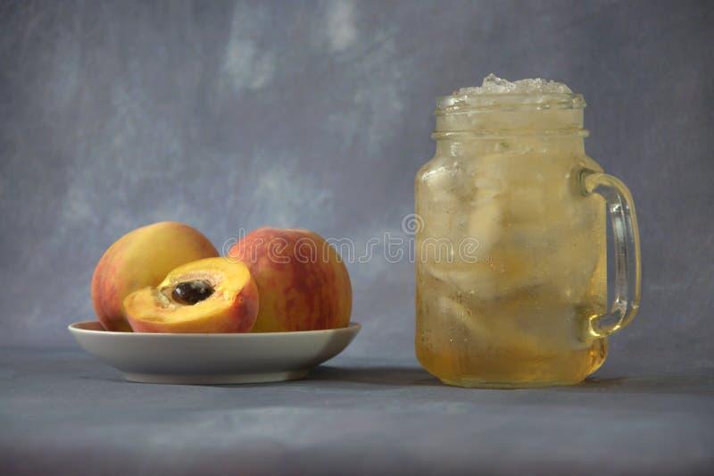 Pêssegos suculentos maduros em uma placa cerâmica e em uma caneca de suco do pêssego com gelo em um fundo abstrato cinzento Close imagens de stock royalty free