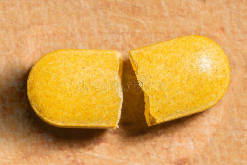 Píldora amarilla quebrada en dos pedazos, fondo de la abstracción imagenes de archivo