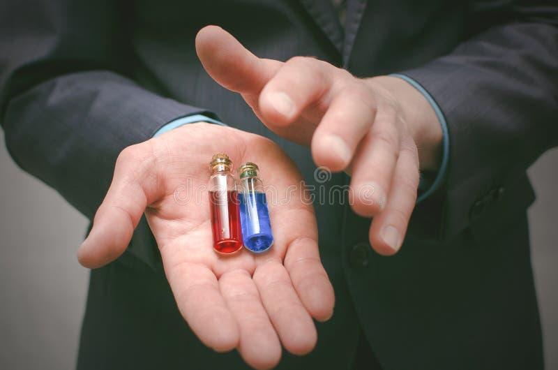 Píldora azul y roja que elige concepto Selección del esteroide o de la droga foto de archivo