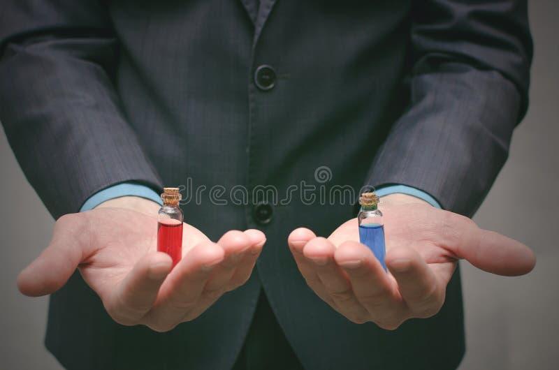 Píldora azul y roja que elige concepto Selección del esteroide o de la droga imagen de archivo