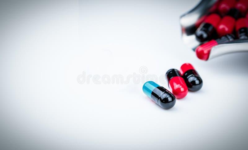 píldora de la cápsula y bandeja azulverdes de la droga con la cápsula rojo-negra Cuidado médico global Resistencia a los medicame fotos de archivo libres de regalías