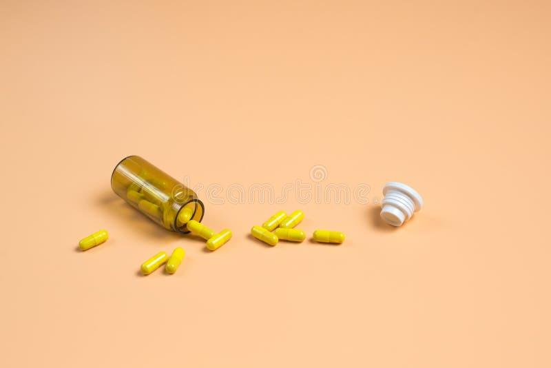 Píldoras amarillas en la botella de cristal en un fondo anaranjado imagen de archivo libre de regalías