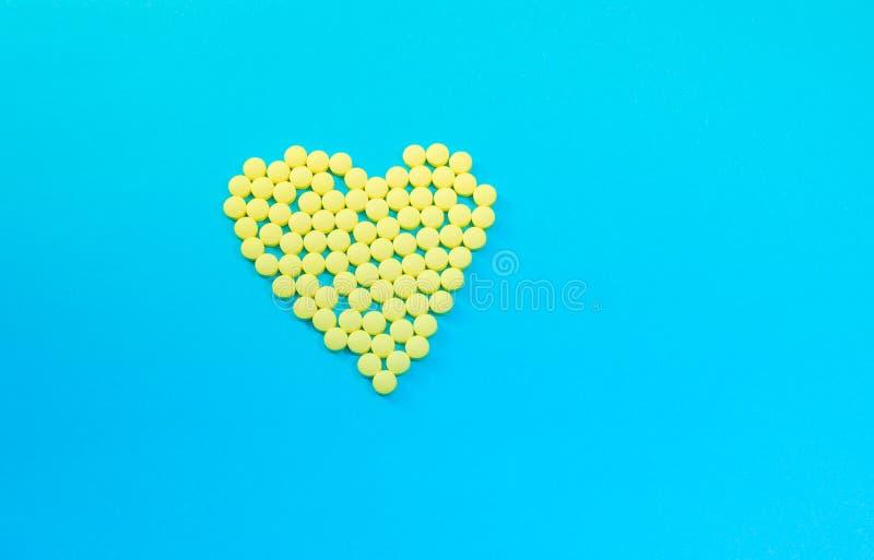 Píldoras amarillas en la forma del corazón foto de archivo