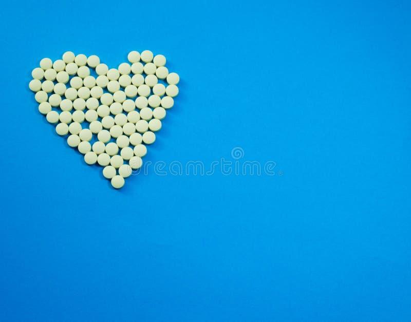 Píldoras amarillas en la forma del corazón fotos de archivo