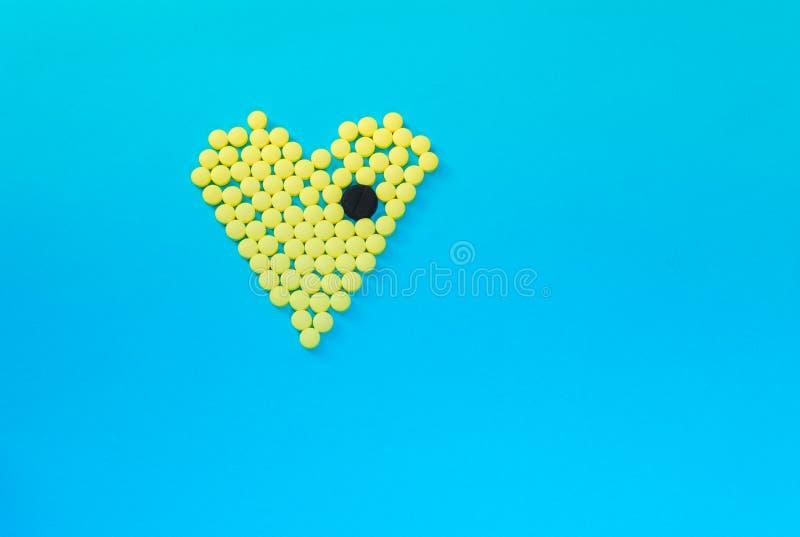 Píldoras amarillas en la forma del corazón con la tableta negra grande imagen de archivo
