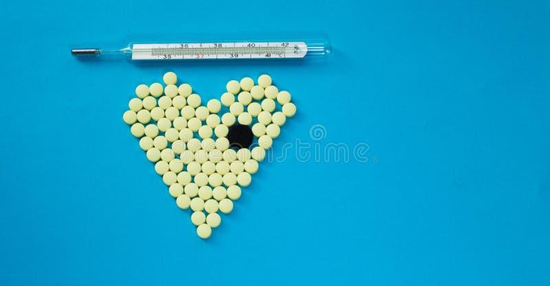Píldoras amarillas en la forma del corazón con la tableta negra grande y el termómetro médico fotos de archivo libres de regalías