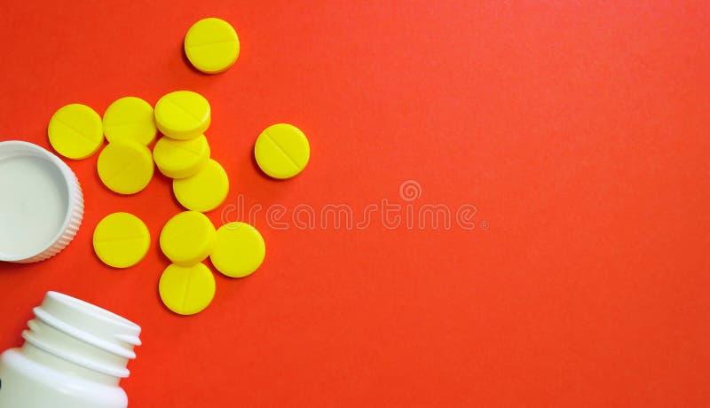 Píldoras amarillas y botella blanca con el espacio de la copia en fondo rojo fotos de archivo