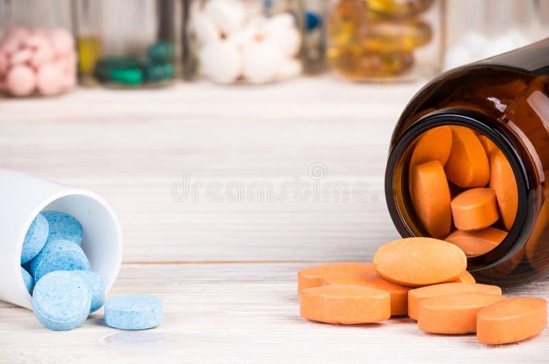 Píldoras anaranjadas en el envase de cristal del marrón oscuro y píldoras azules en el pla foto de archivo libre de regalías