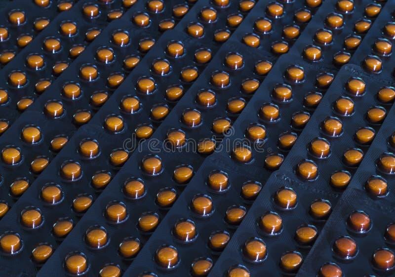 Píldoras anaranjadas en paquete de ampolla negro fotografía de archivo libre de regalías