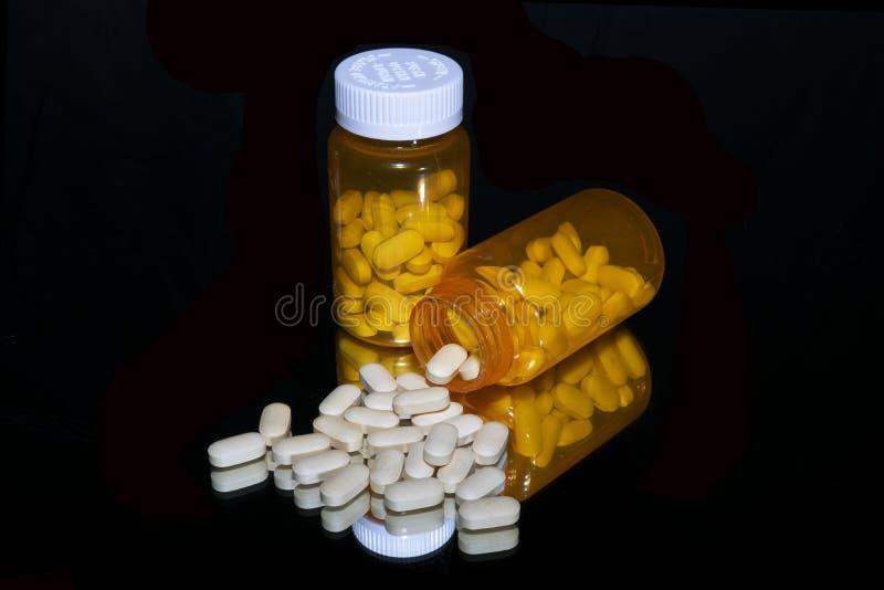 Píldoras blancas derramadas con las botellas anaranjadas en negro imagenes de archivo