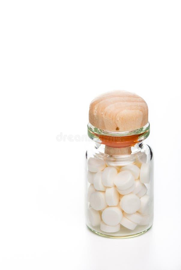Píldoras blancas en el envase de cristal con el top de madera fotografía de archivo