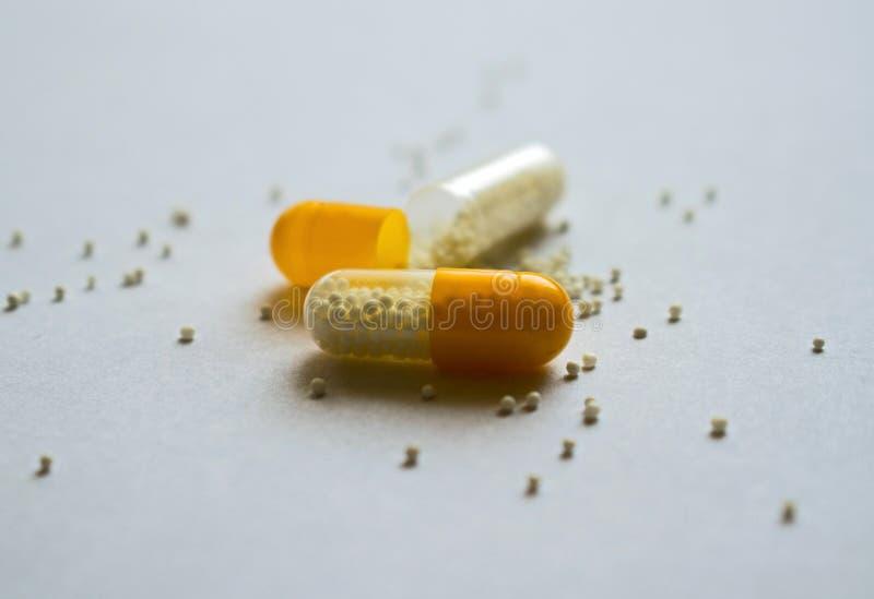 Píldoras blancas y amarillas en el fondo blanco Blanco y amarillo imagen de archivo libre de regalías
