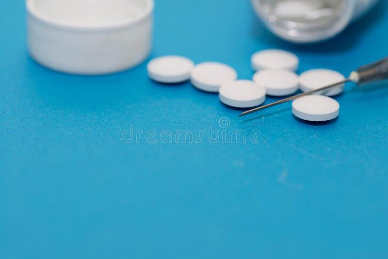 Píldoras blancas y cierre de la jeringuilla encima del tiro macro en fondo azul fotografía de archivo