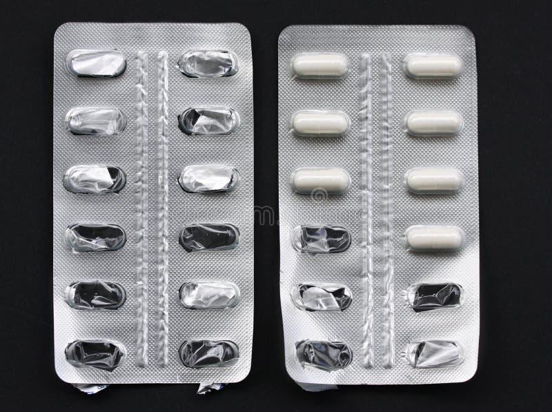 Píldoras de la medicina en píldoras de los paquetes en las cápsulas de aluminio del paquete de ampolla Algún nuevo y algún vacío  fotografía de archivo
