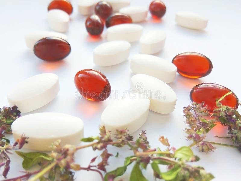 Píldoras de la medicina herbaria con las hierbas naturales secas en el fondo blanco Concepto de medicina herbaria y de suplemento imagenes de archivo
