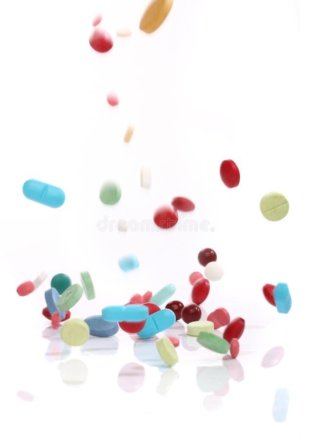 Píldoras de la medicina que caen imagenes de archivo
