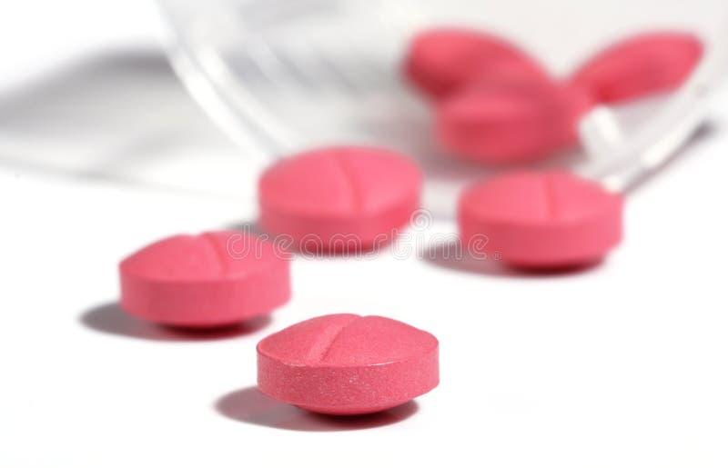 Píldoras de la medicina que desbordan una botella fotografía de archivo libre de regalías